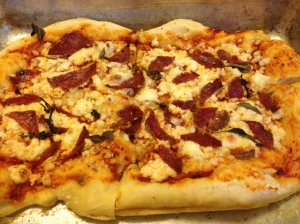 Homemade pizza with the cheese and a medley of salamis and fresh basil